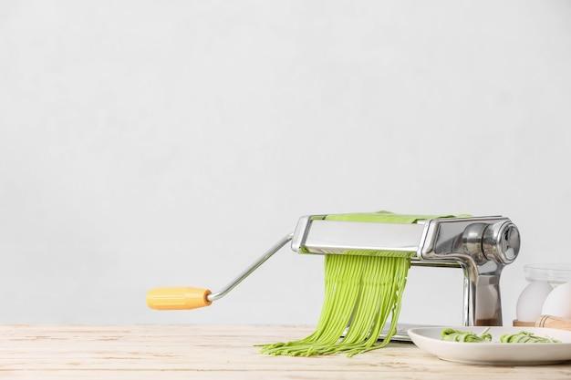 Máquina de macarrão com massa em fundo claro