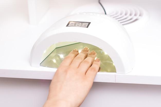 Máquina de manicure polonês com lâmpada uv durante o processo de secagem de unhas em salão de beleza
