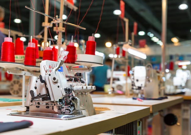 Máquina de overloque na fábrica de costura, ninguém. costurar roupas. tecido têxtil. fabricação de tecidos, tecnologia de costura