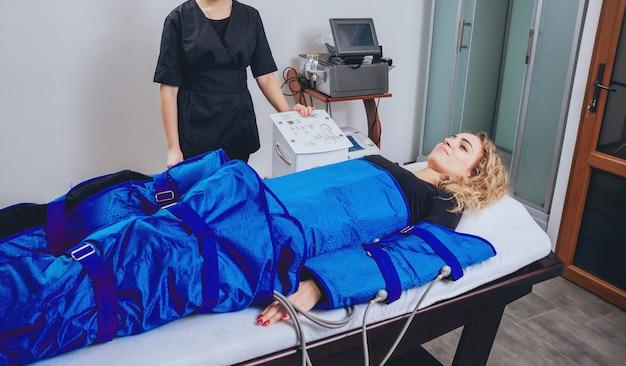Máquina de pressoterapia na mulher no centro de beleza