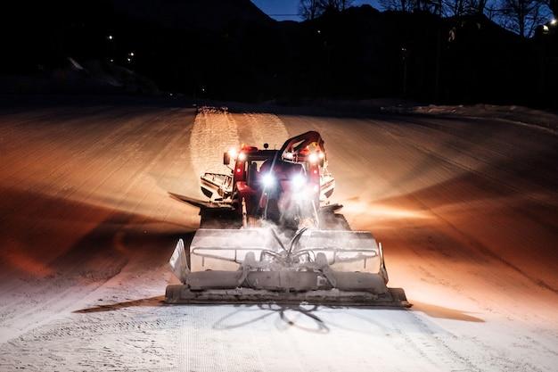 Máquina de ratrack snowcat fazendo neve à noite na estação de esqui