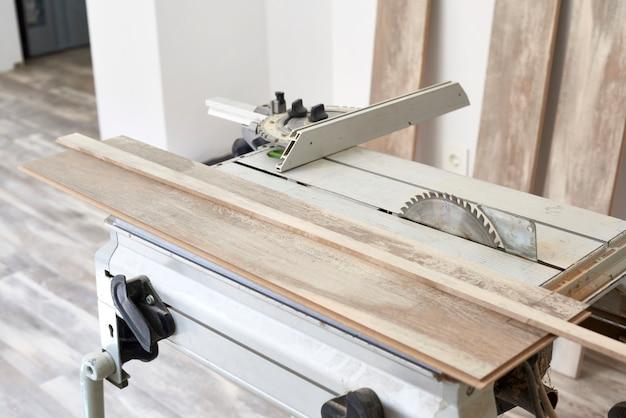 Máquina de serra circular para cortar madeira. o processo de instalação de laminado de madeira no chão. construção de casas.