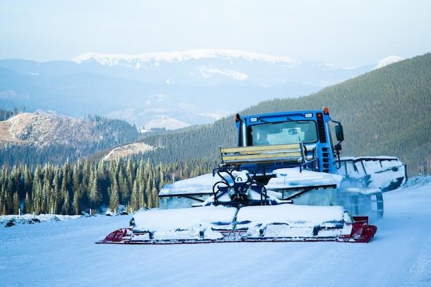 Máquina de soprador de neve trabalhando na estância de esqui com florestas e montanhas