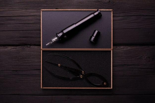 Máquina de tatuagem em um fundo preto de madeira. tubos, pontas, apertos para tatuagem.