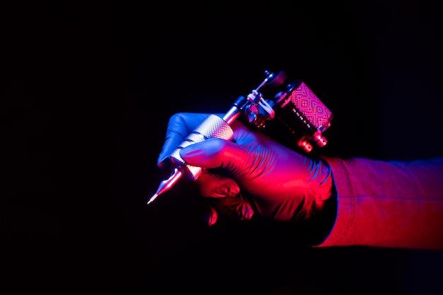 Máquina de tatuagem popular mãos femininas fundo escuro permanente