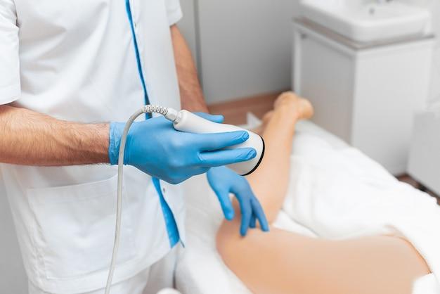 Máquina de ultrassom para correção de forma corporal nas mãos de um médico.