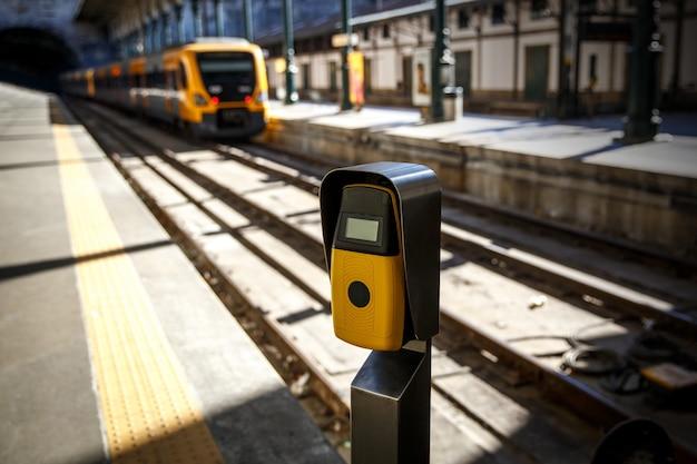 Máquina de validação de bilhetes em amarelo profundo em um trem de saída de estação ferroviária