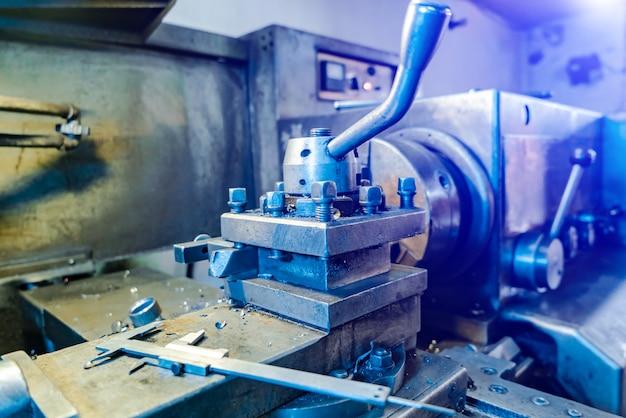Máquina do torno do cnc na oficina com fundo azul.