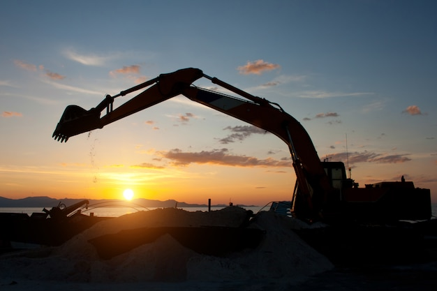 Máquina escavadeira sobre esteiras, fazendo trabalhos de terraplenagem