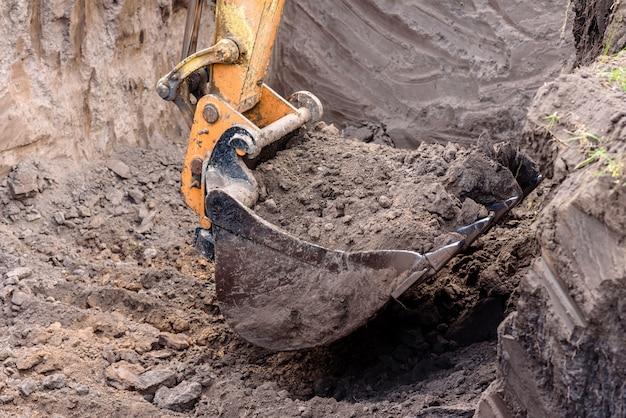 Máquina escavadora amarela em um canteiro de obras contra o céu azul. a escavadeira moderna realiza trabalhos de escavação no canteiro de obras