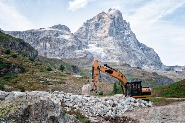 Máquina escavadora estacionada na estrada com a montanha ao fundo