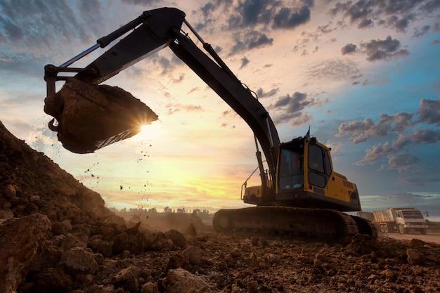 Máquina escavadora na caixa de areia durante obras de terraplenagem no canteiro de obras.