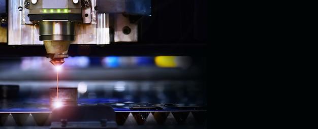 Máquina industrial de corte a laser enquanto corta a chapa com a luz brilhante, espaço livre no lado direito para texto.