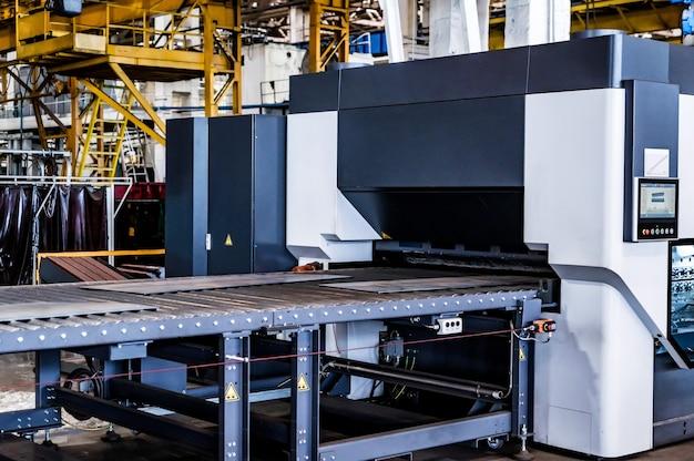 Máquina niveladora de peças na sala de montagem em uma grande planta industrial de fabricação de tratores e colheitadeiras