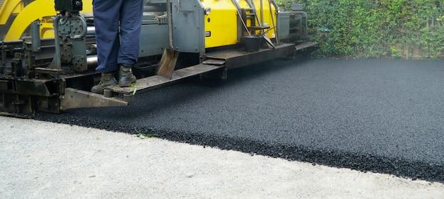 Máquina pavimentadora de asfalto durante obras de reparação rodoviária