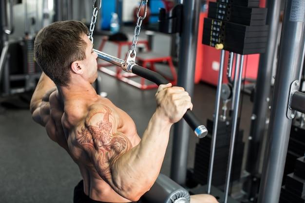 Máquina puxadora de ombro. homem de aptidão malhando lat pulldown formação no ginásio. exercício de força na parte superior do corpo para a parte superior das costas.