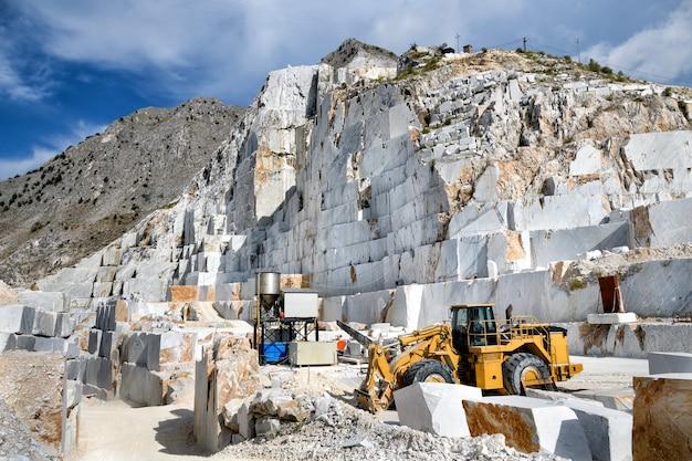 Maquinaria industrial em uma pedreira de mármore a céu aberto, minerando mármore de carrara branco no norte da toscana, itália