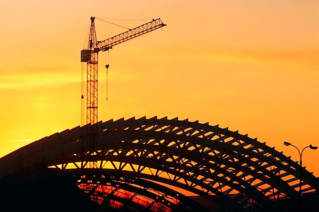 Maquinaria industrial, guindaste de construção e arena de esportes do quadro.