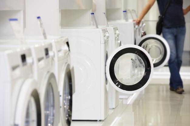 Máquinas de lavar roupa na loja de eletrodomésticos e comprador desfocado