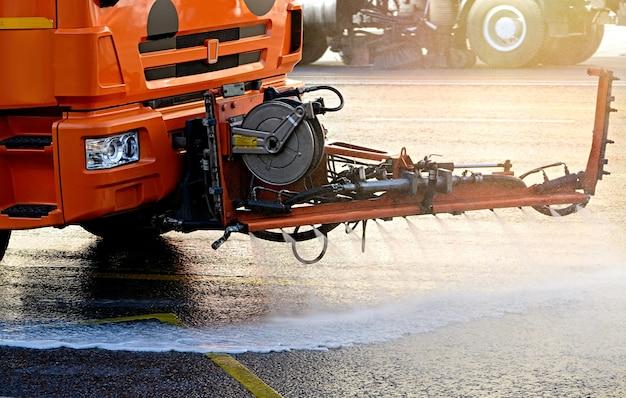 Máquinas de limpeza limpa a estrada de asfalto da cidade com spray de água no início da manhã