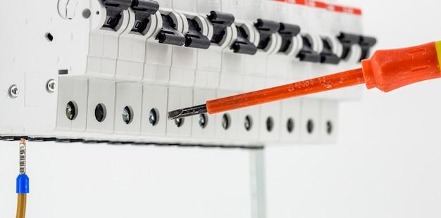 Máquinas elétricas, interruptores, isolados no branco, close-up, conecte o cabo do marcador a um dispositivo com uma chave de fenda vermelha