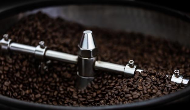 Máquinas profissionais de resfriamento torrado girando e movimento de grãos de café marrom fresco perto até foco seletivo