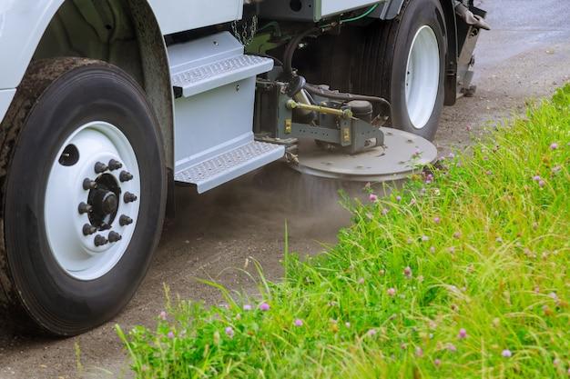 Máquinas varredoras de limpeza lavam estrada de asfalto com spray de água no foco suave da cidade
