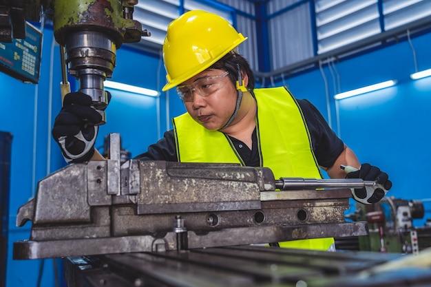 Maquinista asiático em traje de segurança operando tornos profissionais em uma fábrica de metalurgia,