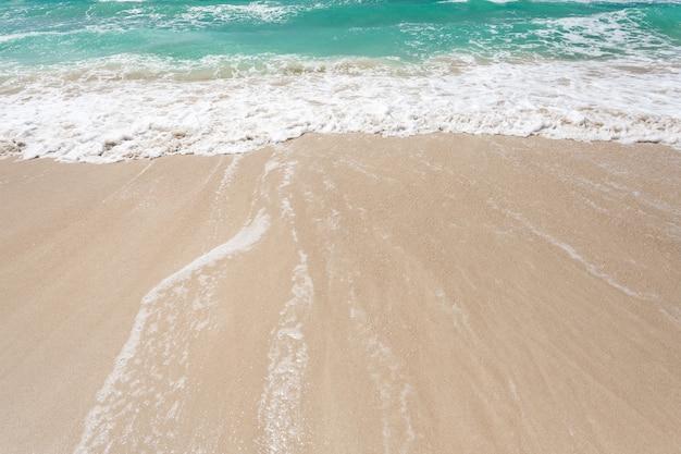 Mar, água azul-turquesa, surfe em uma praia arenosa