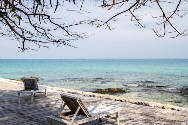 Mar azul calmo e cadeira de praia de madeira branca