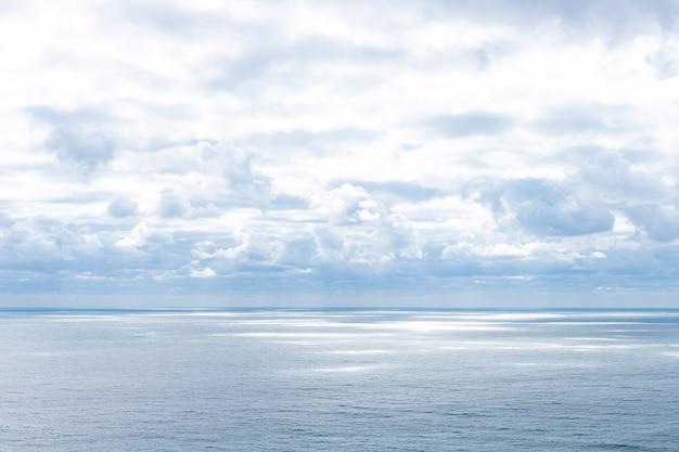 Mar azul calmo e nuvens no céu