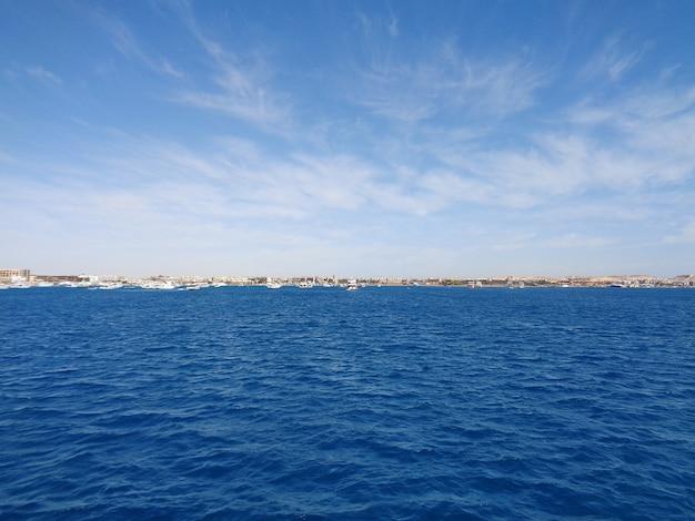 Mar azul, cidade e barcos no horizonte