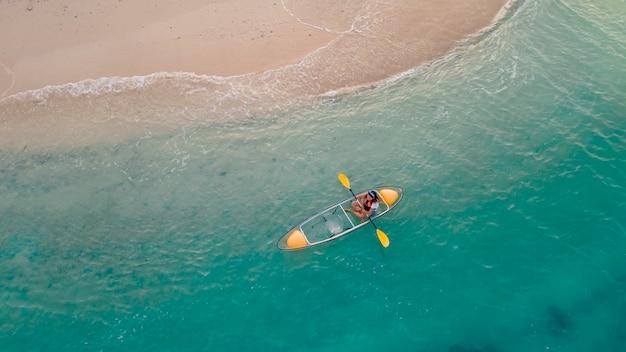 Mar azul com caiaque flutuante transparente perto da praia de areia, pessoa com colete salva-vidas no barco
