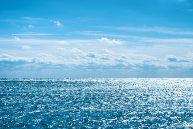 Mar azul com céu e nuvens. fundo natural da água