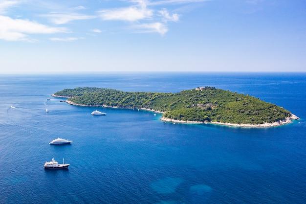Mar azul com iates brancos na costa da dalmácia da ilha lokrum do mar adriático em dubrovnik, croácia