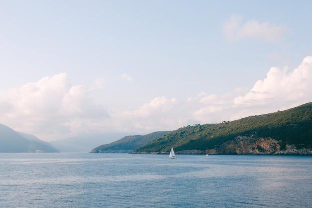 Mar azul com vista para montanhas verdes, um veleiro branco flutua à distância