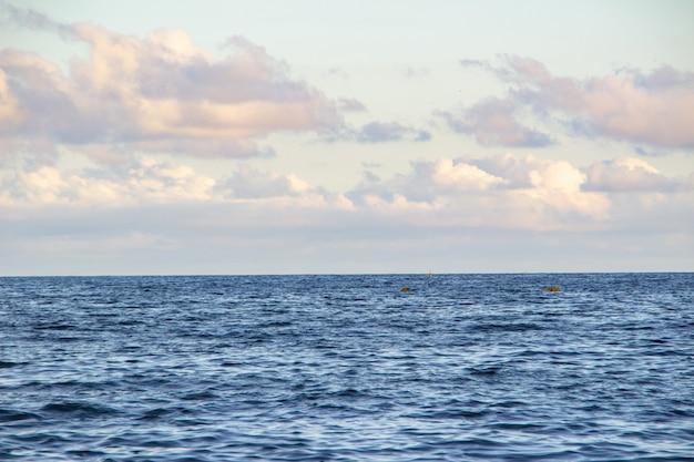 Mar azul da praia do copacabana com o céu azul com algumas nuvens para o fundo.