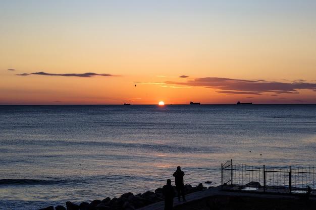 Mar azul e nuvens no céu, nascer do sol no horizonte