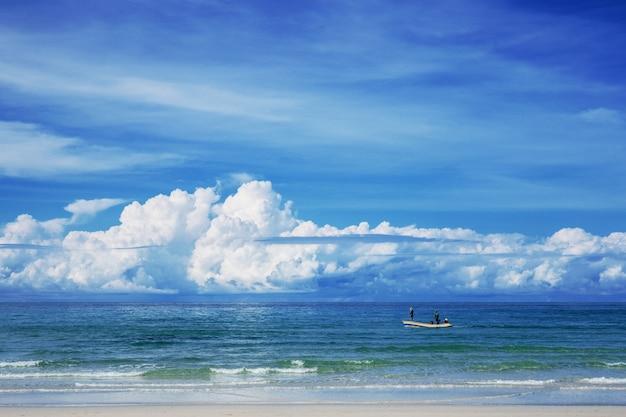 Mar azul e pescadores com céu.