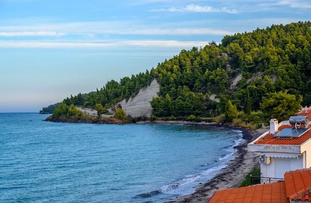Mar azul e praia com floresta em fourka scala, halkidiki, grécia