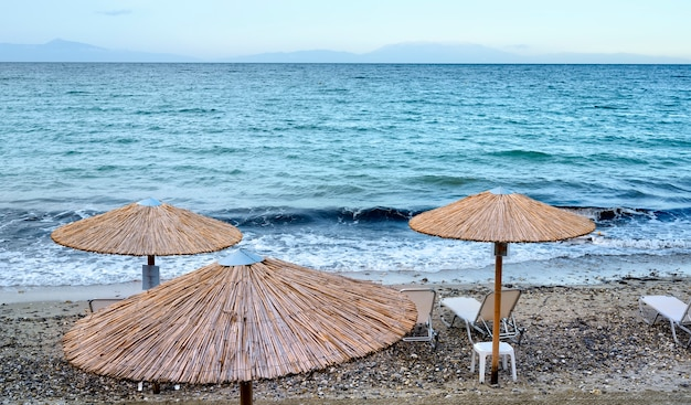 Mar azul e praia com guarda-sóis em fourka scala, halkidiki, grécia