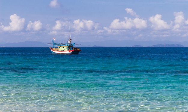 Mar azul e um pequeno barco de pesca.
