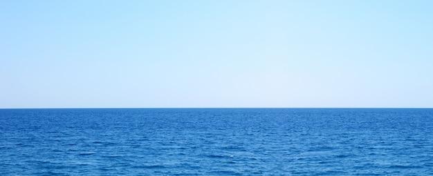 Mar azul escuro e céu azul claro