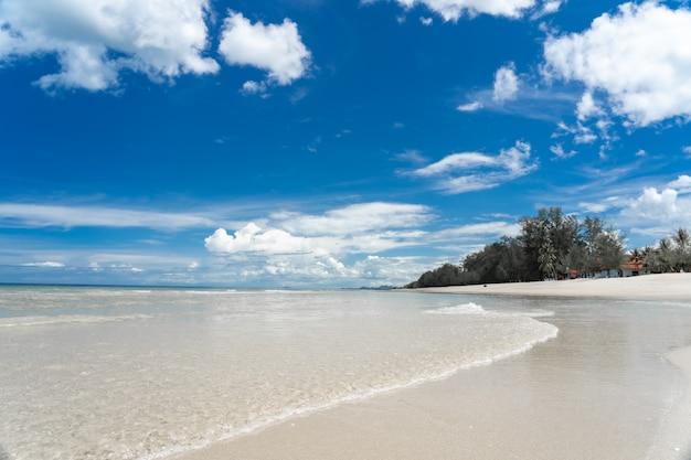 Mar azul turquesa com areia branca e céu ensolarado