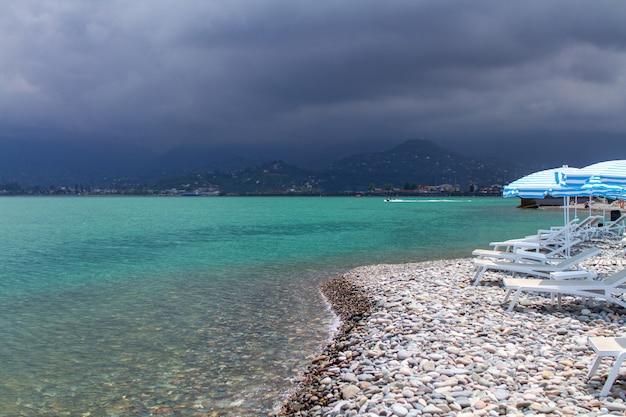 Mar azul-turquesa e pebble beach com guarda-sóis e cadeiras de praia contra montanhas. férias no mar
