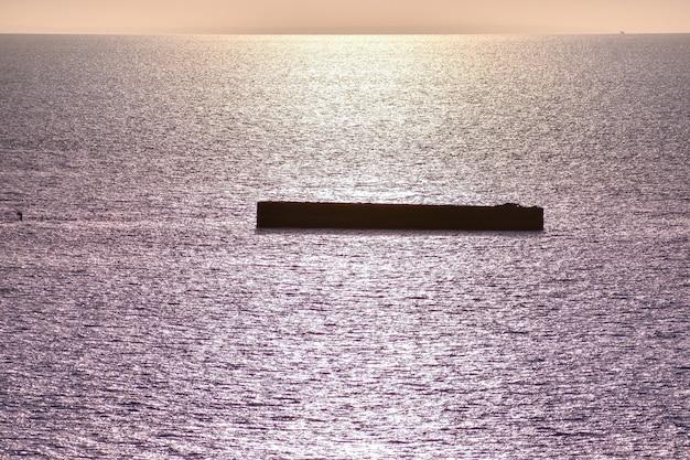 Mar calmo com céu do sol. horizonte colorido sobre a água e a parede do atlântico. normandia, frança.
