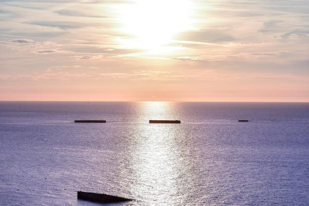 Mar calmo com céu do sol. horizonte colorido sobre a água e a parede do atlântico.