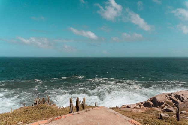 Mar cercado por colinas cobertas de cactos e rochas sob um céu azul e luz do sol