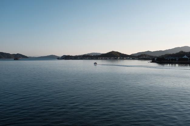 Mar cercado por colinas cobertas de prédios e vegetação sob um céu azul