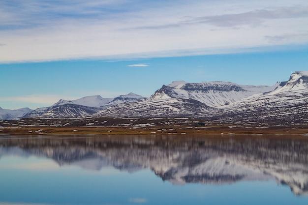 Mar cercado por montanhas rochosas cobertas de neve e refletindo na água na islândia